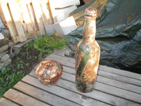 Maan alta vanhan sokkelin vierestä löytyi ehjänä vanha vihreä lasipullo ja herätyskello.