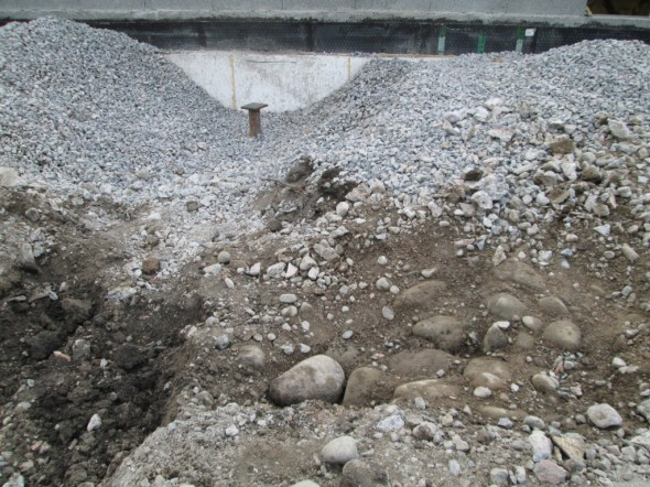 Kuvassa ala vasemmalla kaivantoa autokatoksen anturalle. Oikealla on kivistä tehty polku (ihan niin kuin Italiassa näkee tällaisia). Anturan tiellä olleet kivet on jo viety pois, ja yksi kivi väännetty irti. Miksi maan alle ja itse asiassa talon alle on tehty kivistä polku? Ehkä kyseessä on kivipesä, jonka tarkoitus on ollut imeyttää maahan vanhan saunarakennuksen pesuvedet. Tosin savimaa ympäröi joka puolella, eli en tiedä miten hyvin kivipesä on toiminut. Tai sitten kivien tarkoitus ihan joku muu.