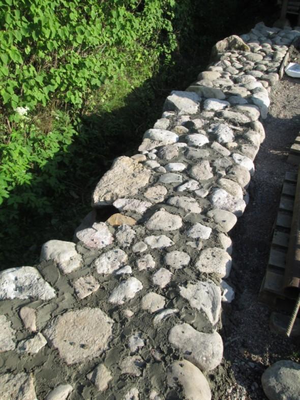 Betonia jäi jonkin verran yli, ja ylimääräisellä betonilla laitettiin pyöreitä kiviä tontin laidalla olevan avo-ojan viereen.
