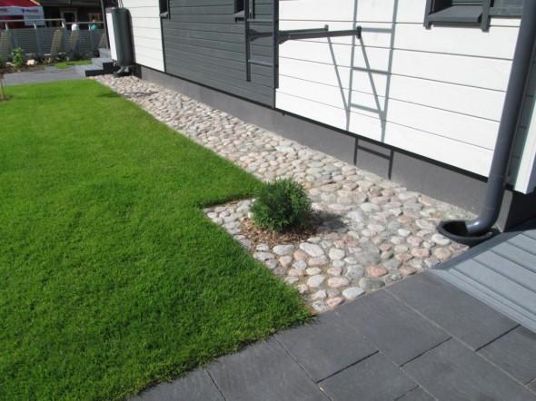 Kauniisti rajattu nurmikko ja hyvin onnistunut kivetys.