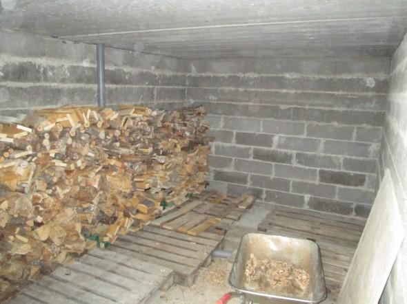 Ensimmäinen hyötykäyttöön saatu tila oli kellarin puuvarasto. Tässä on jo vähän koottuna tontin raivauksesta syntyneitä polttopuita ja kaikenlaista laudan pätkää. Terassin alla olevan huoneen kokonaistilavuus on noin 26m3, eli puuta mahtuisi aika paljon jos tämän tilan sulloisi polttopuuta aivan täyteen. Puukasan takana näkyvä viemäriputki kerää katetulta terassilta vedet pois, jos sinne joskus jotain tulee.