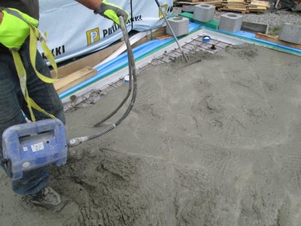 Itsetasoittuvan HT-betonin levittämistä vibralla ja haravalla. Ja levisihän se, kun on riittävän järeät työkalut.