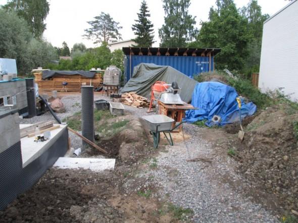 Betonimylly ja mahdollinen suihkulähteen paikka terassin edestä katsottuna, siis tulevan puutarhapolun paikalta. Nyt sepelillä peitetty työmaapolku on melkein oikealla kohtaa jo sekin, eli päälle tai hieman taloon päin tulee loppupeleissä laatoilla katettu kävelypolku.