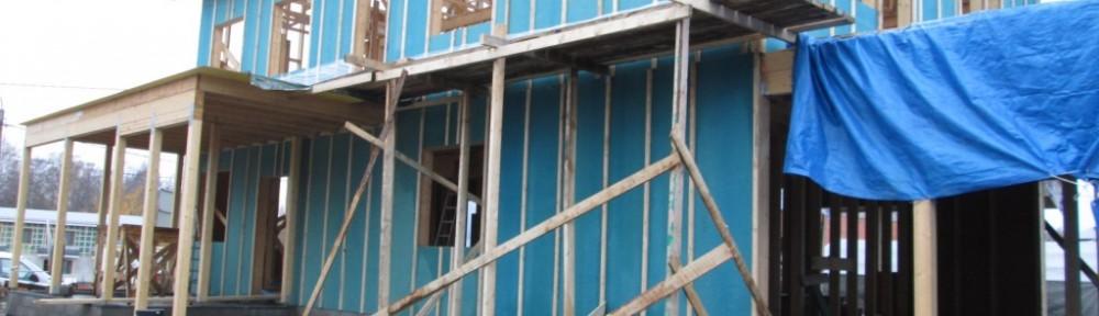 Tuulensuojalevyt kahdessa kerroksessa. Autokatoksen lujalevyt (paloluokkavaatimus EI 30) puuttuu vielä. Samoin päätykolmiot ovat vielä avoimet, ja tellinkit puuttuu Rekolantien puoleisesta talon päädystä. Tässä etelänpuoleisen seinän tellinkeillä näkyy vähän muovituksia terassilla, niistä tarkemmin seuraavassa kuvassa.