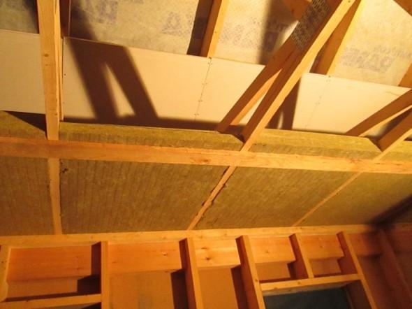 Alla näkyy seinän koolauksia (villat vielä lisäämättä väleihin), yläpohjan jäykät villat, sitten äänilukon kipsilevyt ja ylälaidassa peltikaton alla olevaa aluskatetta.
