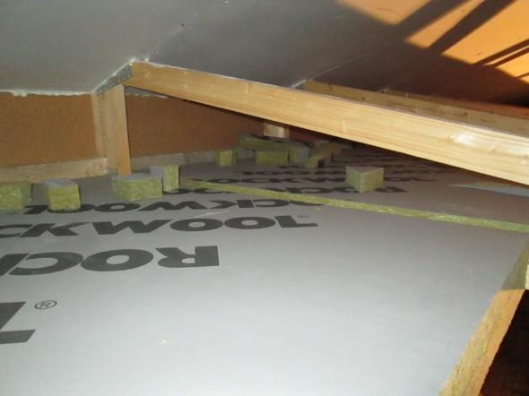 Tässä kuvassa ylhäällä äänilukon kipsilevyt ja niiden päällä jäykkä villalevy. Samaa jäykkää villaa myös yläpohjassa kattotuolien välissä harvalaudoituksen päällä kannattamassa puhallusvillaa. Eli tämä tila tulee puhallusvillaa täyteen. Nyt tilaa täyttämässä jo muutamia hukkapaloja.
