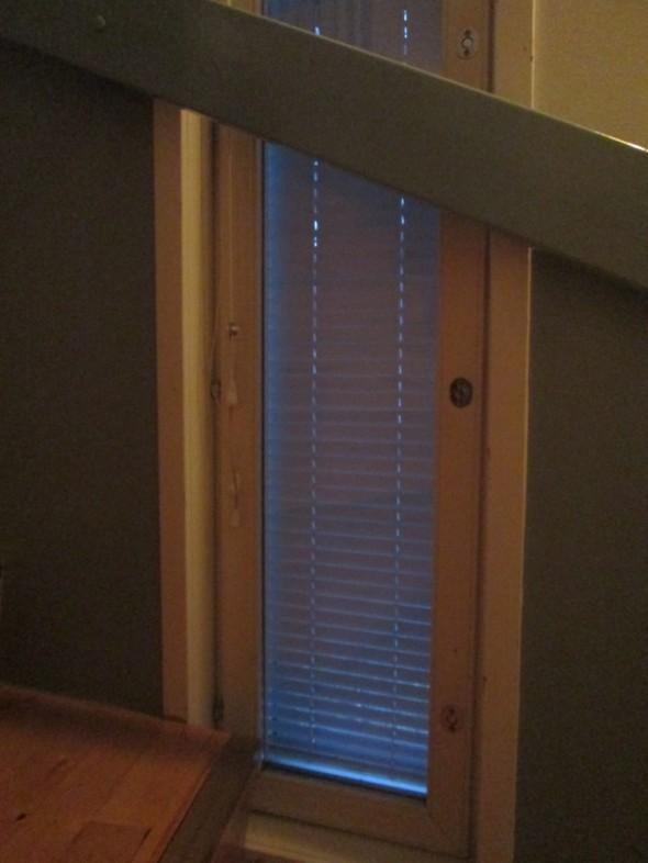 Vuokra-asunnon portaikko. Sama ikkuna. Jos se menisi joskus rikki, ei sitä ihan helposti oteta pois saranoilta ja ikkunan vaihtaminen ja/tai peseminen sisäpinnoilta vaatisi kaiteen irrottamisen.