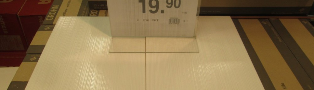 """Seinän päävärinä valkoinen laatta, jossa poikittaisia """"sudin jälkiä""""."""