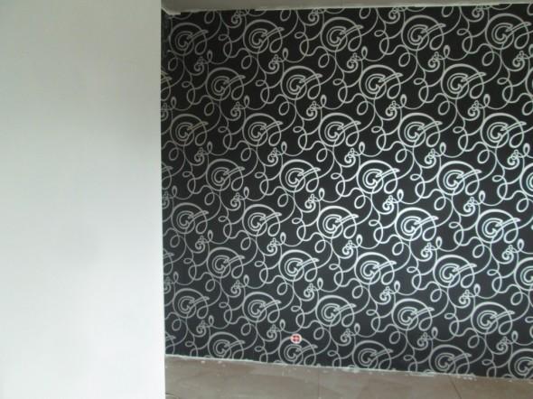 Master-bedroom seinän värisävy valittiin niin, että tapetilla oleva harmaa sävy on täsmälleen sama mitä seinänkin väri. Eli tapetin saumakohdassa kiehkuroiden väri tavallaan hyppääkin seinälle. Saumapiste oviaukolla ei ole vielä valmis, mutta idean näkee periaatteessa tästäkin kuvasta.