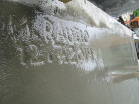 """Ja kun betoni on vielä pehmeää, niin pitäähän se signeerata... :-) Tässä lukee """"M.Rautio"""" ja päivämäärä. Itse asiassa kaikilla talon neljällä asukkaalla on samalla alkukirjaimella alkava etunimi, eli jokainen voisi lyhentää nimensä samalla tavalla."""