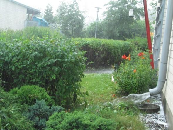 Rännin täydeltä vettä ja rakeita talon seinustalla.