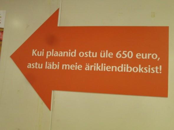"""Yritysmyyntipisteen seinällä oleva kyltti lähempää. Siinä lukee vapaasti suomennettuna että """"kun aiot ostaa yli 650 eurolla, tule meidän yritysasiakaspisteen kautta""""."""