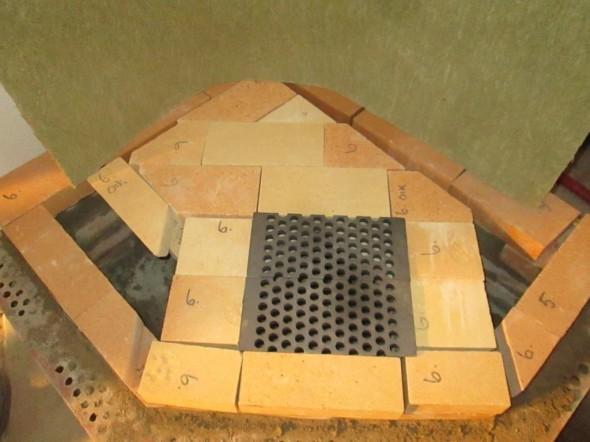 6-kerros menossa. Tässä kohtaa vaalean keltaiset tulenkestävät tiilet erotetaan keskikerroksen oranssista tiilikerroksesta 10mm palovillalla. Keskikerros puolestaan erotetaan punatiilisestä kuorikerroksesta omalla palovillalla, ja takan taakse tulee 50mm palovilla. Takka tietysti lämpenee yhdellä polttopuusatsilla aina yhtä paljon, mutta villaa käyttämällä sisäosat lämpenevät vielä enemmän, ja luovuttavat lämpöä villan läpi pidempään. Samalla ulkokuori pysyy viileämpänä, eikä tule polttavan kuumaksi. Takan lämpövarauksesta on jäljellä 60 tunnin kuluttua vielä 25%. Kolikon kääntöpuolella tietysti se, että jos lämpöä tarvittaisiin nopeasti, niin se ei tällä isolla ja villaeristetyllä kuorellisella takalla onnistu ihan niin helposti.
