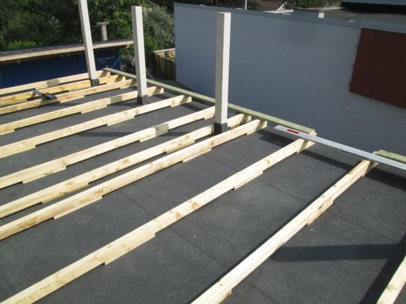 Bitumi on nostettu myös käsikaidepuun tolppien ympärille. Tästä homma jatkuu normaaliin tapaan terassin lattian laudoituksella, johon käytetään painekyllästettyä puuta.