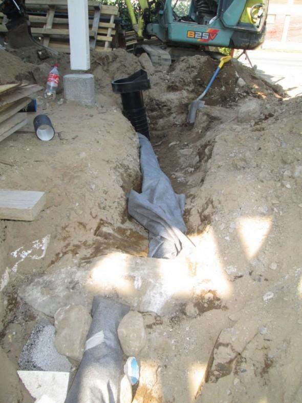 """Luovana ratkaisuna salaoja katkeaa vanhan sokkelin kohdalla. Toinen pää kallistaa toiseen suuntaan ja toinen toiseen suuntaan. Yläpuolinen """"töpö"""" on niin lyhyt, että se menee sadevesikaivon kautta sadevesiviemäriin. Salaojaputkien ympärillä on suodatinkangas, ettei hiekka mene putken sisään."""