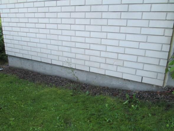 Talon päädyssä seinän tiiliverhoilussa on alimman tiilirivin joka kolmas tiili jätetty oikeaoppisesti kokonaan ilman laastia. Nyt sitten seuraavaksi tehdään reikiä tähän tiiliseinän alla olevaan betonipintaan alapohjan alapuolelle, ja imetään radonit sitä kautta pois.