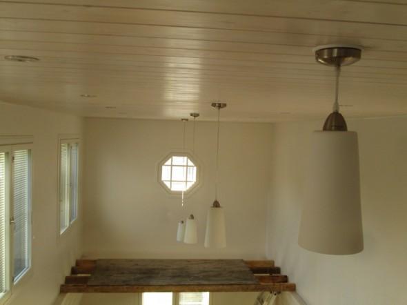 """Laskeva lamppurivi korkean olohuoneen katossa. Täsmälleen suoraan linjaan vedettynä se on vähän niin kuin tilateos, jota katsellessa silmä lepää. Valaisimen muodoksi valittiin korkea ja kapea, joka korostaa huoneen muotoja. Riippuvien lamppujen kanta on saman väristä metallia mitä LED-spottien ympärykset. Katon paneelit on käsitelty valkolakalla, joka jättää puun syyt näkyviin. Kattopaneelien materiaalina on kuusi, eli ei isoja oksia. Niin... Miten korkeassa olohuoneessa pestään yläikkunat? Tai vaihdetaan kattolamput? Kuvan alareunassa näkyy vastaus, eli määrämittaisten pattienkien päälle ruuvataan vanerilevy. Nyt levyä käytetty lamppuhommissa, eli ikkunanpesussa levy olisi ikkunan puoleisessa seinässä kiinni. Tarvittaessa voi laittaa vaikka 2 levyä rinnakkain. Tämän """"tellinkin"""" kasaamisessa ei mene kahdelta mieheltä ja kahdella tikapuulla kuin 10 minuuttia."""