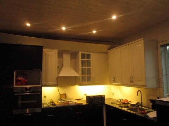 """Keittiön valaistusta. Katossa 3000K LED-spotit. Kaappien yläsokkeliin (kuvassa levyt kaadettu) tulee vielä LED-nauha koko keittiön pituudelta, mutta sitä ei vielä ehditty laittaa paikoilleen. Yritin sovitella yläkaappien alalistan taakse 4000K LED-nauhaa ja 3000K LED-nauhaa, ja lopuksi hylkäsin kaikki LED-nauhan vaihtoehdot. Valituksi tuli kaappien levyiset kapeat loisteputkivalaisimet, joiden valo oli tasaisempi ja silmää miellyttävämpi. Vaikka LED-nauhan saa tässä kohtaa (kaappien alalista) erittäin hyvin piiloon ja erittäin epäsuoraksi, niin silti se lopputulos on vaan """"pistemäinen"""" kun sitä puolen metrin päästä joutuu katsomaan. Loisteputkessa ei tätä lieveilmiötä ole. Tai ainakin itse kääntelin LED-nauhat joka suuntaan ja kokeilin kahta eri väristä nauhaa - enkä saanut onnistumaan, jostain raosta aina falskasi LED:n pistemäisyys. Mutta jos ne pistemäiset heijastumat ei silmää häiritse, niin ei siinä sitten mitään, kyllä silloin LED-nauha soveltuu erittäin hyvin myös keittiön yläkaappien alle työtasoa valaisemaan."""