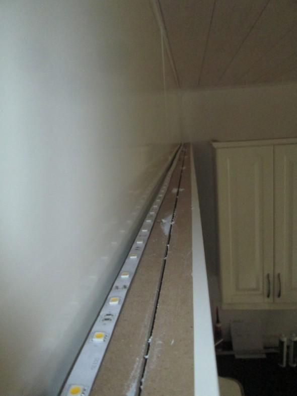 Tässä lähikuvaa siitä, miten LED-valaistus on toteutettu valkoisten kaapistojen päällä. IKEA:n ylälistoissa on jo valmiina ja ilmeisesti LED nauhaa varten tehty sopiva ura. Yläsokkeli on nyt kuitenkin liian lähellä (jos keittiö tehtäisiin uudelleen, sitä pitäisi siirtää 5-10 cm vasemmalle). Nyt tässä toteutustavassa LED-pisteiden valo peilautuu yläsokkelin pintaa vasten, ja lopputulos ei ole ihan niin kaunis, mitä se pienellä hienosäädöllä voisi olla. Toki yläsokkeli on muuten hyvän näköinen, kun se on tuotu niin eteen mitä suinkin mahdollista.