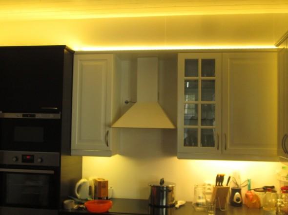 """Jos ei kiinnitä huomiota muuttopäivän jälkeiseen sekasotkuun keittiön pöydällä, niin tässä kuvassa näkyy tai pitäisi näkyä muutama juttu valaistukseen liittyen. Ylävasemmassa kulmassa LED-nauhan valo näyttää hyvältä ja tasaiselta, siellä LED-nauha on yläsokkelista etäämmällä noin 30cm, kun tumma kaapisto on paksumpaa kuin valkoinen. Valkoisen kaapiston kohdalla LED-nauha kurvaa aivan kiinni yläsokkeliin - josta loistaa pistemäinen valokuvio, joka ei ole enää niin hieno kuin vasen yläkulma, jossa valo heijastuu joka suuntaan tasaisena, eikä näy mistä suunnasta se tulee.  Kaapistojen alalaidassa on loistevaloputket, joista tulee tasainen valo - LED:llä toteutettuna tässä näkyisi pistemäisiä laikkuja mm. niissä kaapiston pinnoissa jotka valojen päissä menevät seinää kohden ja joutuvat kulmakohdassa """"liian lähelle"""" LED-nauhaa. Loistputkia ei kuitenkaan voi laittaa esim. kaapistojen päälle, koska ne näkyisivät sieltä, ja valojuovasta tulisi katkonainen (jos ei saa putkia limittäin). Eikä loisteputkissa noissa tiloissa ole mitään järkeä muutenkaan."""