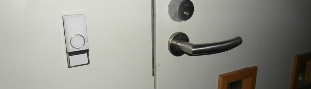Ovipainikkeen voi asentaa ulko-ovelle siististi joko 2-puolisella teipillä (tuli mukana), tai 2 pienellä ruuvilla (nekin tuli mukana). Tässä käytetty 2-puolista teippiä.