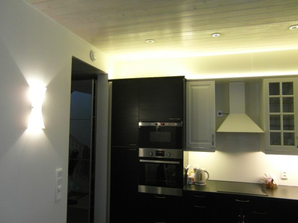 Tiimalasin halogen-valo yhtenä lähtökohtana on samalla noin 3000K värisävyllä keittiön yläkaappien päällä LED-nauha ja yläkaappien alareunassa kunkin kaapin levyiset loisteputket. Yritin ensin sovitella loisteputkien paikalle myös LED-nauhaa, mutta LED-nauhan pisteet alkoi paistamaan vastaan kaikista heijastavista pinnoista, joten hylkäsin LED-nauhan tässä kohdin. Loisteputki antaa tasaista valoa ilman pistejono efektiä. Kaappien yläreunassa pistejoho efektiä ei synny, koska valo törmää kattopaneelin ja yläsokkeliin, ja imeytyy siihen riittävästi.