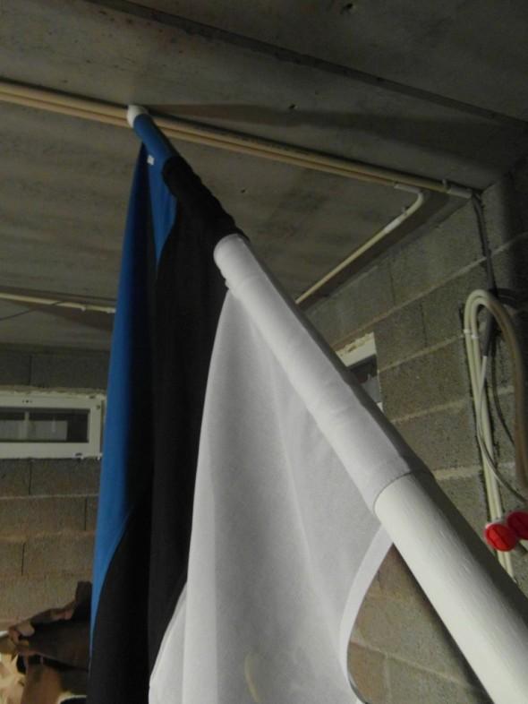"""Viron lippu asettuu vinotankoon """"kireän sukan"""" avulla nopeasti ja helposti. Lippu pitää ujuttaa tyvestä ylöspäin, koska yläosan nupin kautta se ei mahdu tulemaan."""
