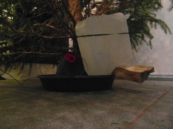 4 litran lisäjuoma joulukuuselle. Alun perin tuulilasin pesunestettä sisältänyt kanisteri ylösalaisin ja tuettuna klapilla ja narulla niin, että lautasen kuivuessa sinne pääsee pulpahtamaan aina lisäannos vettä. Kun veden pinta nousee kuusen jalassa, korvausilmaa ei pääse kanisteriin, ja veden tulo loppuu. Sama tapahtuu uudestaan aina kun kuusi kuluttaa vettä ja pinta laskee kuusen jalassa.