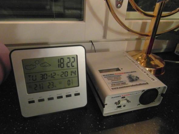 Keittiön työtaso talon keskimmäisessä kerroksessa. Vasemmalla oma sisä/ulkolämpötilamittari, sen vieressä oikealla Suomen radonhallinnan tietokone, joka tekee kerran tunnissa lämpötila ja radonmittauksen. Mittauksen päättyessä mittaushistoriasta ja olosuhde muutoksista saadaan käyrät.