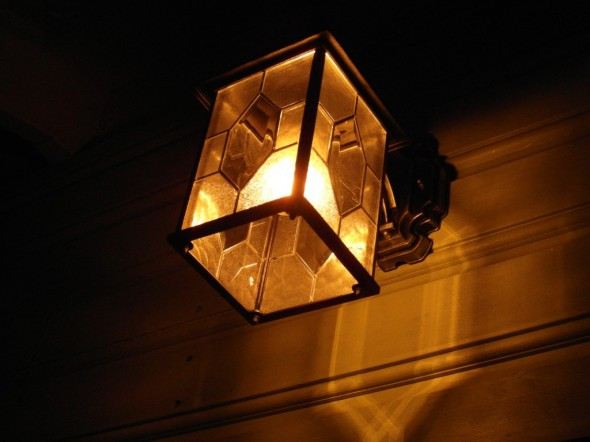 Sähköä on kulunut tänä talvena suhteellisen vähän, vaikka pelkästään tässä ulkovalossa oleva hehkulamppu kuluttaa yksinään 25 vattia (silloin kun se on päällä - ei tämä jatkuvasti pala). Minusta juuri tällainen takkatulen värisävy eli noin 3000 Kelviniä joka tästä vanhan ajan hehkulampustakin tulee, niin minusta tämä valon väri on kaunis ja luo lämmintä tunnelmaa. Talon esikuvana on muutenkin ollut vanhan ajan eli 1920-luvun talot Helsingin Kumpulassa ja Käpylässä, joten myös kuvassa näkyvään vuorilautaankin on höylätty antiikkikaarella olevaa koristekuviota päälle.