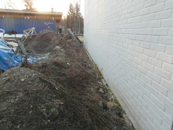 Nurmikkotöissä tarvittavat maa-ainekset odottavat levittämistä naapurin talon seinustalla. Etualalla savista multaa, takimmainen kasa vähän parempaa multaa. Aivan pintaan voi tarvita hakea vielä kaupastakin multaa. Lopuksi naapurin talon seinustalle on tarkoitus istuttaa riviin muutama tuija, ja valaista ne tuijat ja naapurin talo maahan asennettavilla spot-valoilla. Naapurilta jo kysyin luvan, että heidän talon seinään saa heijastaa valot. Tontin raja kulkee suunnilleen siinä missä seinäkin.
