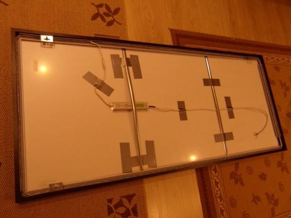 Peilin takana olevat LED-asennukset. Peilin puukehyksen sisäpuolella kiertaa alumiinilista, johon led-nauha on liimattu kiinni. Vasemman puoleisen metallikiskon alla on muuntaja, josta menee syöttöjohto peilin kehän ympäri kulkevalle led-nauhalle, ja toinen pää menee tällä hetkellä väliseinän läpi keittiön halogen lampulle.