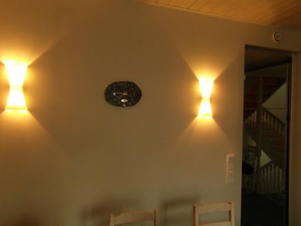 Sama väliseinä, jossa on eteisen peili kiinni, näyttää toiselta puolen eli keittiön puolelta tällaiselta. Halogeenivaloja ohjataan valokatkaisijasta. Sähkö tulee ensin katkaisijaa lähinnä olevalle valaisimille, josta se jatkaa eteenpäin vasemmalle halogeenille. Ja nyt sähköjohdon matka jatkuu myös seinän läpi eteisen puolelle peilin taa, jonne on asennettu ledit. Eteisen peilin ledit syttyy siis samalla, jos keittiön seinällä olevat halogeenivalot laittaa päälle. Kaikki sähköjohdot jäivät piiloon väliseinän sisään.