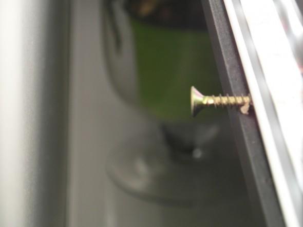 Peilin molemmissa alakulmissa - alumiinilistan ja puupokan väliin kierrettynä on leveäkantainen ruuvi. Se toimii topparina, ja sen avulla voi myös kätevästi säätää peilin kallistuskulmaa. Jos haluaa, että peilin kuvakulma avautuu enempi alaspäin, näitä alakulman ruuveja voi kiertää syvemmälle. Nyt peili on vaakatasossa eikä sitä ole kallistettu mihinkään, jolloin ruuvin pituuden verran jää nyt tilaa ledvalolle päästä ulos peilin takaa.