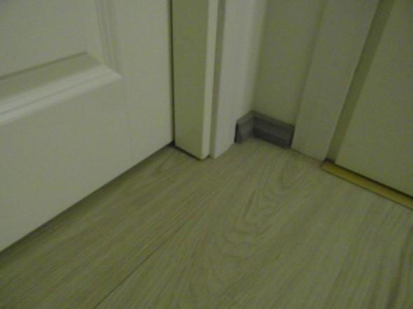 Makuuhuoneen ovi ja WC:n ovi yläaulasta katsottuna. Makuuhuoneeseen päin menee yhtenäinen lattia ilman kynnystä, ja tuuletusrako toimii oven alla.