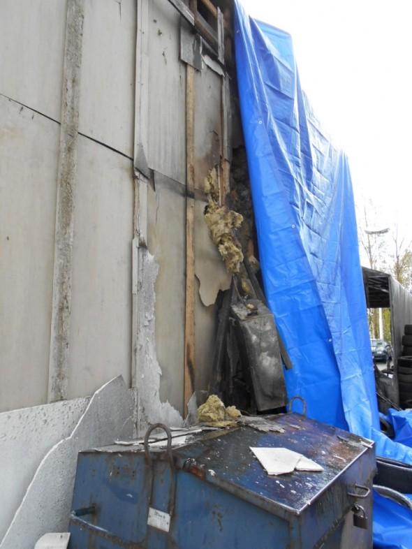 Palomiehet ovat koukkineet villoja irti seinästä, jotta ovat päässeet palaviin pesäkkeisiin käsiksi paremmin. Tämän jälkeen timpurityönä otetaan loputkin sammutuksen jäljiltä märät villa pois vahinkoalueelta.