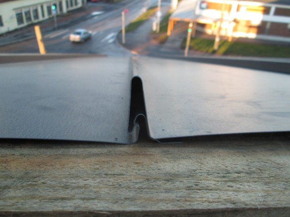 Tässä lähikuva lukkopontista.  Ruuvin läpiviennit jäävät alemman pontin oikealle puolelle, jonka päälle naputellaan seuraavan pellin korkeampi pontti päälle. Lumiestelistat ja aurinkopaneelien kiinnitykset laitetaan puristamalla näihin harjanteisiin kiinni, eikä kattoon tehdä yhtään reikää.