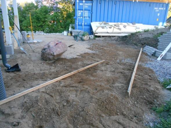 Hiekkapedin tasoitus ja kaltevuuden mittaus pitkien lautojen avulla. Maan pitää pikkuisen kallistaa talosta pois päin.