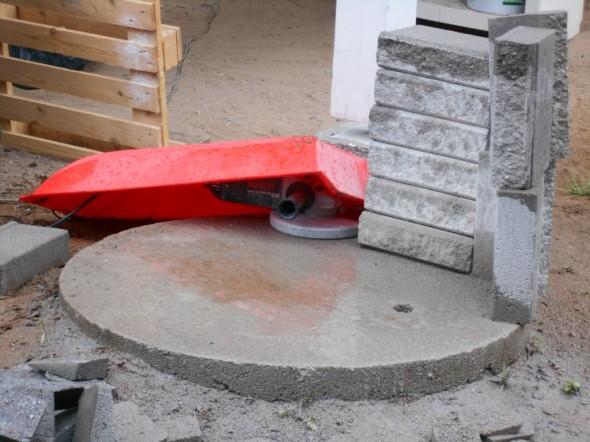 Timanttilaikka tauolla ja sateelta piilossa pulkan alla. Sateella rakentaminen on vähän sellaista väkisin rakentamista. Kivitöissä pölyä lentää sadekelillä toki paljon normaalia vähemmän, eli oli siitä sateesta hyötyäkin.