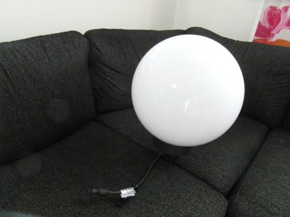 """Iso valkoinen pallovalaisin """"istutettuna"""" sohvatyynyjen väliin. Kokoluokka hahmottuu tästä ehkä vähäsen?"""