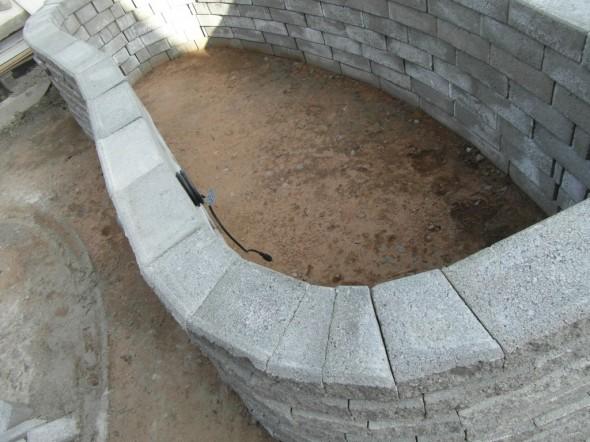 Ylimmän kerroksen kivipinta jäi latomisen jäljiltä tämän näköiseksi. Etenkin sisäkurvissa kivien välissä olevat tyhjät tilat nauravat sekä istutusaltaa sisään päin (ei haittaa mitään - sehän täyttyy mullalla), että myöskin ylöspäin, joka kyllä näkyy. Jos ei haittaa silmää, niin ei tämän voi jättää näin. Itse ajattelin kuitenkin valaa tähän betonista kaarevan kannen, jolloin kivien raot katoaa näkyvistä, ja samalla ylimmästä rivistä tulee jäykkä. Jolloin alimmatkaan rivit eivät voi liikkua, eikä istutusallas voi kaatua kumolleen. Valaminen on pelkkä varmuustoimi - eli ei se kaatuisi mihinkään ilman valamistakaan. Kun käsin kokeilee tuljuttaa, niin kaareva muoto on niin tukeva, ettei se tulju eikä heilu mihinkään päin. Ja jokainen ladontakerros kallistaa sisälle päin pikkuisen.