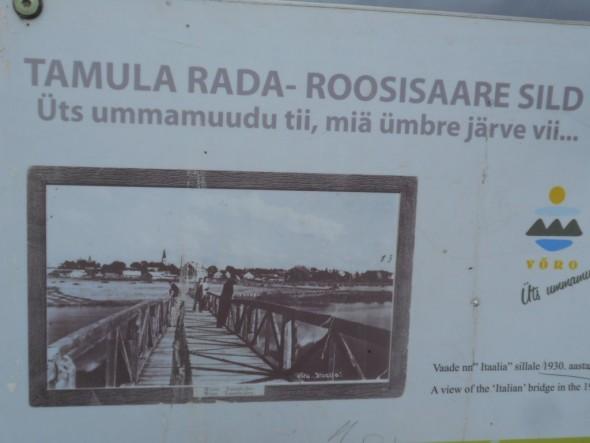 """Roosisaaren silta 1930-luvulla. Otsikossa lukee paikallisella Võrun kaupungin murteella että """"Üts ummamuudu tii, miä ümbre järve vii..."""". Tulkitsen, että se vapaasti suomennettuna tarkoittaa, että """"yksi ympyrän muotoinen tie, mikä ympäri järven vie...""""."""