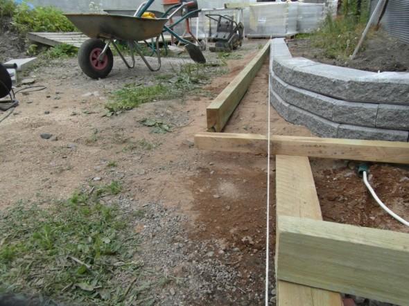 Kivimuurin rakentaminen suoraan linjaan vaatii tarkkuutta. Jos tekisi pienellä kaarella sinne sun tänne, niin se onnistuu aina ja menee aina oikein. Kukaan ei huomaa jos joku kaari on pari senttiä pielessä. Mutta jos suorassa linjassa on muutaman sentin mutka, sellaisen virheen huomaa kaikki. Alakulmassa puutarhaletkuun sukeltava sähköjohdon pätkä toimittaa vetonarun virkaa. Vedän siitä sitten aikanaan Easy Connect pihavalot vielä seuraavaankin istutusaltaaseen.