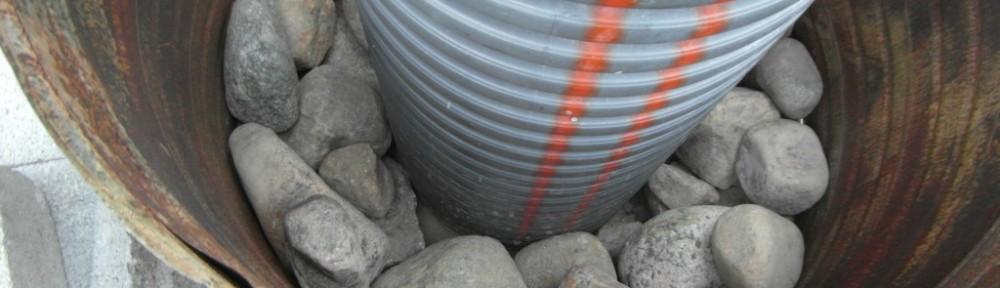 Tässä lähtötilanne. Tynnyrin puolikkaan pohjalle on ladottu eka kerros isoista kivistä, ja sitten siihen päälle toinen kerros pienempiä kiviä ulkoreunoille. Seuraavaksi sisäpuoli täytetään betonilla, ja survotaan siihen sitten sidokseksi vielä sisäkaarelle uusia kiviä märkään betoniin sisään. Kauniin kivet ulkokehälle - ja rumat sisälle. Kivet kastellaan ennen betonin valamista, jotta tartunta olisi hyvä.