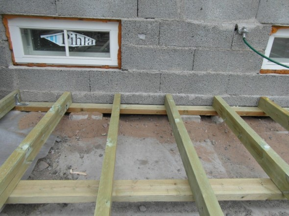 Kellarin ikkuna asetti paineita rakennelman korkeudelle. Ikkunan alle pitää jäädä 20 cm lumivara. Siitä syystä alemmat runkopuut tulivat nyt suoraan päin maata, eikä niitä voinut suojata oikein mitenkään. Keskelle ei ole tuotu täyttömaata, siinä on styroksin päällä pelkkä suodatinkangas. Jos taloon joskus tulee maalämpö, sitten terassi, suodatinkankaat ja styroksit otetaan ylös, ja tästä kohtaa sitten viedään putket kellarin tekniseen tilaan.