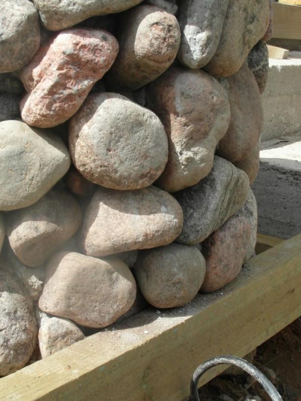 Kivien paino on tuettu terassin runkopuihin. Kaivo painaa ehkä noin 500 kg (?), joten paino ei rasita nyt koko painollaan salaoja kaivoa. Toki ei varmaan esim. painuisi muutenkaan, vaikka yläpäähän tulisikin muutama satakiloa painoa? Kaivossa on kuitenkin pohja, ja se on tukevasti sepelipedin päällä.