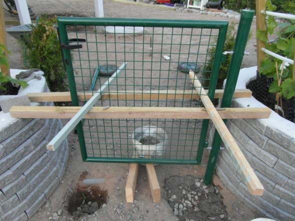 Portin puoleinen jalka valettu betoniin ja portti tuettuna. Portti oli helppo tukea kukkapenkin reunuksiin. Alla syrjällään olevat 6 tuuman pattingit antavat oikeaa korkeutta niin, että sitten kun tässä kohtaa on pihalaatat, niin portin alle jää vielä tyhjää tilaa noin 10 cm. Vasen tolppa valetaan sitten kun oikea on jo kunnolla kiinni ja vasemmat voi silloin tukea muuhun porttiin kiinni, ja täsmälleen oikealle kohdalleen.